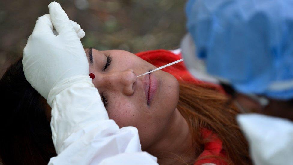 Profissional da saúde insere uma haste flexível no nariz de uma paciente para fazer um teste PCR numa paciente