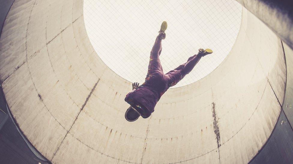 Pessoa em túnel de vento de centro de paraquedismo