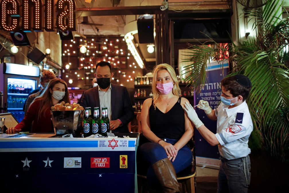 Mulher recebe vacina em bar de Tel Aviv, Israel — Foto: Corinna Kern/Reuters