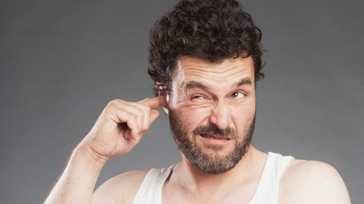 Homem cutuca ouvido - iStock - iStock