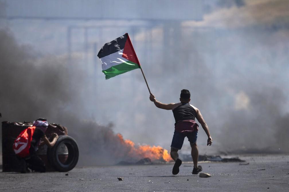 Manifestante levanta bandeira da Palestina durante protesto em Nablus, na Cisjordânia, contra ataques israelenses nesta sexta-feira (14) — Foto: Majdi Mohammed/AP Photo