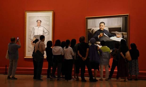 Os visitantes de exposição em Pequim diante de pinturas dos líderes comunistas Mao Tsé-tung e Deng Xiaoping Foto: GREG BAKER / AFP